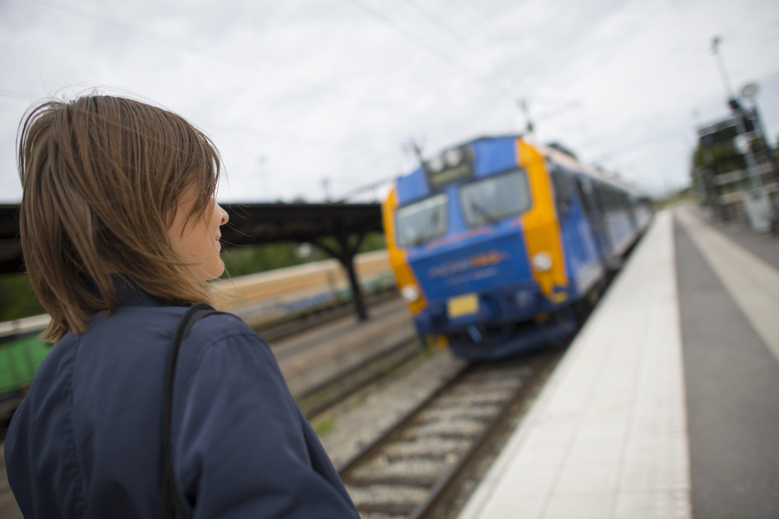 Kvinna på tågperrong Norrtåg blågult tåg